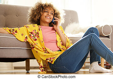 attractive african american woman relaxing at home and talking on cellphone