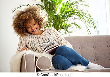 attractive african american woman sitting on sofa reading book
