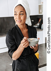 Portrait of attractive african american woman wearing housecoat, having breakfast at home