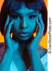 portrait of attractive african american woman with hands on face looking at camera