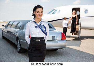Portrait of attractive airhostess standing against limousine...