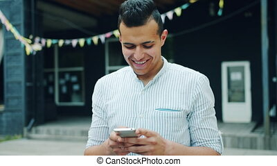 Portrait of attractive Arabian man using smartphone touching...