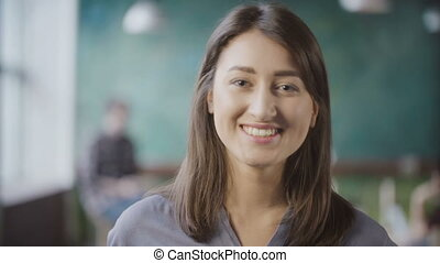 Portrait of attractive Asian businesswoman at loft office. Successful female worker turns, looks around and smiling.