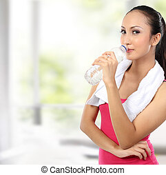 attractive asian smiling woman drinking water