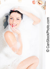 portrait of attractive beautiful sexual blue eyes young woman lying relaxing in the luxury bath with foam happy smiling & looking at camera
