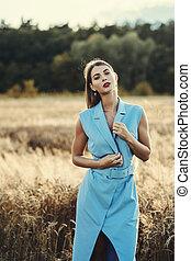 Portrait of attractive blonde woman in blue dress in wheat field.