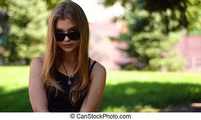 Portrait of attractive blonde woman removes sunglasses looks confident to camera