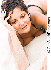 brunet woman lying on a sand