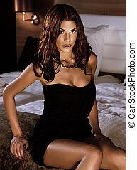 Portrait of attractive brunette beauty sitting in bedroom.