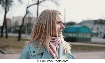 Portrait of attractive Caucasian blonde woman. Anticipation and excitement. Adult 30s female in stylish coat and scarf.