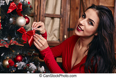 Portrait of attractive caucasian woman brunette, studio shot in red dress putting a christmas balls in christmas tree