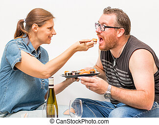 Portrait of attractive  couple  eating japanese food together on the sofa. Couple relaxing on home couch eating exotic food in a stylish home interior