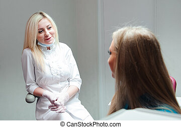 portrait of attractive dentist talking to her patient at clinic