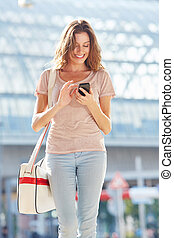 attractive female walking down the street and using smart phone