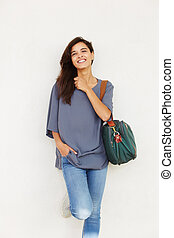 attractive female with handbag leaning to wall and smiling