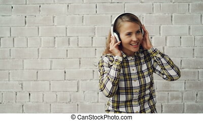 Portrait of attractive girl listening to music through...