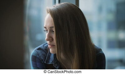 Portrait of attractive girl with long hair. Student sitting near the window and friendly talks with someone.