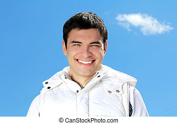 Portrait of attractive happy man on blue sky background outdoors