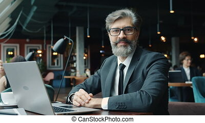 Portrait of attractive mature man entrepreneur wearing suit sitting at table with laptop in cafe