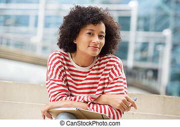 attractive older african american woman sitting outdoors with book and pen