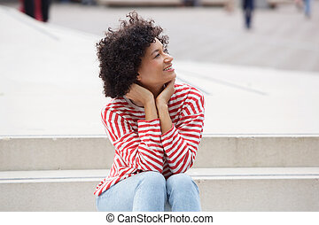 attractive older woman sitting outdoors on steps
