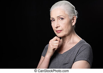 portrait of attractive pensive senior woman isolated on black