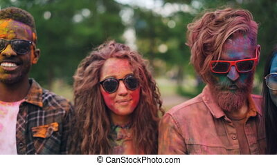 Portrait of attractive people multiracial group with colorful faces, hair and clothing standing outdoors, looking at camera and smiling. Holi festival, party and fun concept.