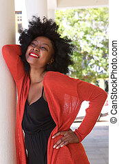 attractive smiling african woman leaning on wall