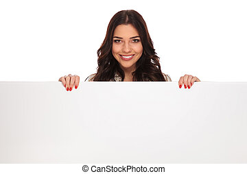 portrait of attractive smiling woman holding an empty sign