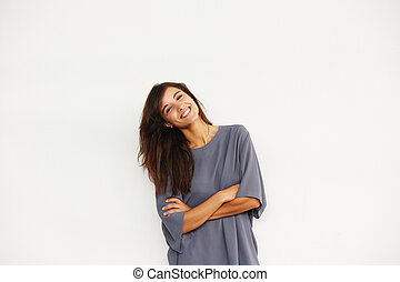 attractive smiling woman standing against wall with arms crossed
