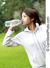 sporty woman drinking mineral water during break after workout