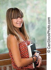 Portrait of attractive teenage girl with book.