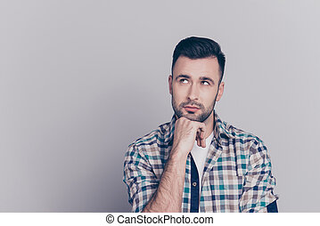 Portrait of attractive, thoughtful man holding arm on chin, having doubts, meditating, looking at copy space, standing over grey background
