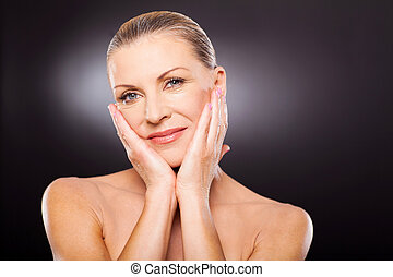 portrait of attractive well-groomed mid age woman touching...