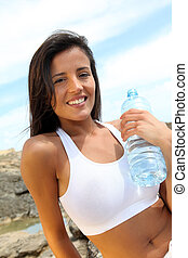 Portrait of attractive woman holding bottle of water outside