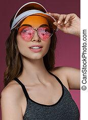 portrait of attractive woman in orange sun visor and ...