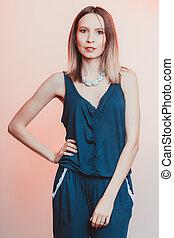 Portrait of attractive woman in overalls.