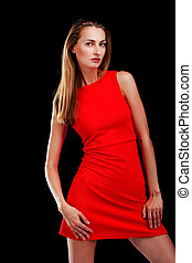 Portrait of attractive woman in red dress on black