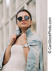 attractive woman in sunglasses and white dress walks through the city streets on a sunny day