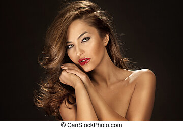 Portrait of attractive woman with red lips and long curly hair