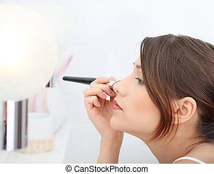 Portrait of attractive young adult woman applying blusher in her bathroom