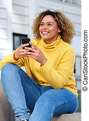 attractive young african american woman holding mobile in city