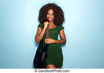 attractive young african american woman in beautiful dress and handbag on blue background