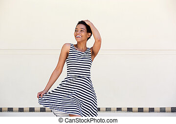 attractive young african american woman laughing in striped dress