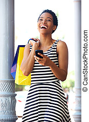 african american woman laughing with phone and shopping bags