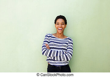 attractive young african american woman smiling against green wall