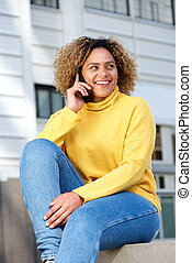 attractive young african american woman talking on cellphone in city