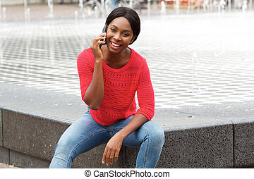 attractive young african american woman talking on mobile phone in the city