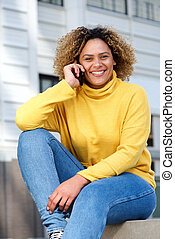 attractive young african american woman talking on phone in city