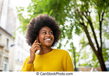 attractive young african american woman talking with cellphone outside